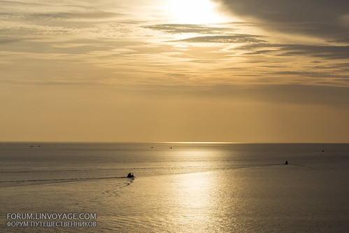 Sunset with fishing boats & palm. Phuket, cape Promthep