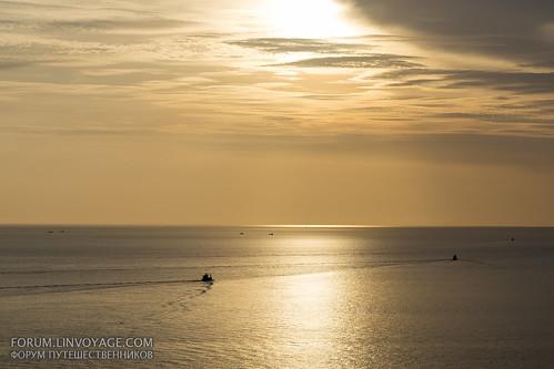Sunset with fishing boats & palm. Phuket, cape Promthep