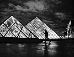 Night intrigue at the Louvre pyramids (Gael Varoquaux) Tags: louvre pyramid louvrepyramid pyramidedulouvre blackandwhite atmosphere spooky walking light clouds paris night silhouette
