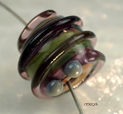 Omega (Laura Blanck Openstudio) Tags: sea urban brown green glass lines festival spiral necklace beads big shiny colorful warm published artist purple bright handmade contemporary teal stripes fine gray arts almond violet lavender dramatic wrapped funky bumpy sage holes odd lilac honey single round winner mysterious huge shows iridescent amethyst chic transparent dots kiln murano rare lampwork multicolor artisan bold whimsical raised petroleum openstudio neutral asymmetric focal pearled annealed openstudiobeads