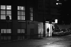In front of the lit railing (pascalcolin1) Tags: paris13 nuit night homme man ombre shadow lumière light photoderue streetview urbanarte noiretblanc blackandwhite photopascalcolin fenetres windows