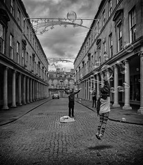 Reaching. (Daz Smith) Tags: dazsmith canon6d bw blackwhite blackandwhite bath city streetphotography people candid canon portrait citylife thecity urban streets uk monochrome blancoynegro mono jumping bubbles girl