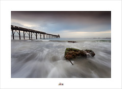 The Tide Will Cut Through The Rock .... Not Because Of It's Power .... But Because Of It's Persistence ... (Maxwell Campbell) Tags: jetty sunrise pier landscape ocean beach longexposure rock