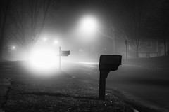The bright lights diffused by fog (LostOne1000) Tags: neighborhood night silhouettes road silhouettescedarrapids mailbox blackwhite iowa unitedstates foggy fog light cedarrapids us