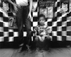 Candy Store, New York (Grandiloquences) Tags: williamklein klein americanartists americanart americanphotographers americanstreetphotographers americanfashionphotographers streetphotography streetphotographers streetscenes candystores cornerstores bodegas cigarettes chesterfields chesterfieldcigarettes kents kentcigarettes 7up checkerboards 20thcentury 1950s 1950sfashion boys children child newyorkchildren kids newyorkkids childhood signs signage newyorkstreetscenes shops 1950snewyork americanphotographs blurry blurred