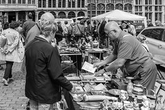 Making a Choice (gwpics) Tags: people blackandwhite bw monochrome person mono commerce belgium market streetphotography lifestyle belgian antwerp society antwerpen socialdocumentary socialcomment antiquesmarket streetpics strasenfotograpfie