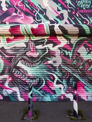Smokin' (Steve Taylor (Photography)) Tags: smoking fingers captainkris embassy roller shutter cigarette teeth face ash smoke art graphic mural streetart weird strange man newzealand nz southisland canterbury christchurch lines