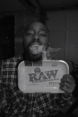 'All We Smoke Is Raw' (miranda.valenti12) Tags: all we smoke is raw papers smiling happy smile weed blunt paper smoking smokey teeth plaid posing sitting basement black white