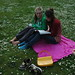 Smiling girls reading a book at Greenlake, with a daisy chain in a field of flowers, Seattle, Washin
