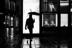 Silhouette with umbrella (PIXXELGAMES - Robert Krenker) Tags: newspaper news cafe kaffee vienna wien snapshot unknown candid portrait portret schwarzweiss blackandwhite blacknwhite bnw fujifilm fujinon filmsimulation lifestyle street streetstyle urban streetphotographer streetphotography biancoenero silhouette man umbrella rain rainy night nightshot