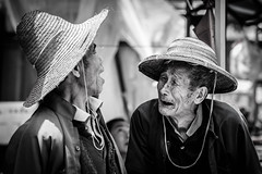 Two old friends (malaholic) Tags: china friends blackandwhite monochrome market conversation talking wrinkles oldmen hunched strawhats xingping