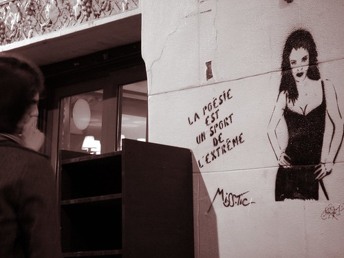 Provocative street art by Miss Tic is stenciled on a wall on Rue Mouffetard in Paris.