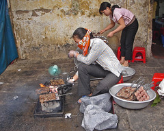 cooks (michale) Tags: hanoi vietnam street cooking market woman women fire smoke grill barbecue meat wall sidewalk bandana handkerchief scarf hands hibachi gloves eat fan blow