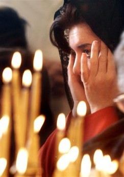 Jordanian Christian woman reacts during prayers at the Greek Orthodox church in Amman, Jordan, Sunday, Nov. 13, 2005