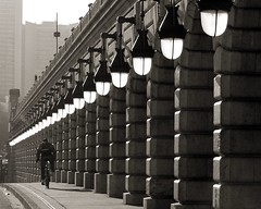 Lights & Columns (Hughes Lglise-Bataille) Tags: blackandwhite bw paris france topf25 bike bicycle backlight topf50 been1of100 olympus 2006 fv5 repetition streetphoto f80 e500 topv1000 v1400