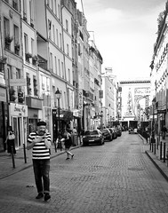 Rue St Denis (ijp01) Tags: france paris 10arrondissement ruestdenis portesaintdenis streetscene blackandwhite cobblestone apartmentbuilding windows parisian stripes monument arc architecture cars sidewalk cellphone iconic