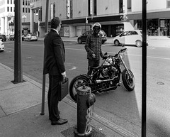 Lifetstyles and Longings (Szoki Adams) Tags: montreal monochrome placevillemarie pvm whitecollarworker motorcycle harley hog helmet plaidshirt shinyshoes firehydrant longing discussion blackandwhite bw blackwhitephotos sunnyday shade streetphotography street streetphoto canong15 canon candid downtown suit jeans outdoors pavement envy talking urban welldressed expressive youngman