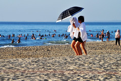 Down to the beach (Roving I) Tags: travel sea tourism sunrise walking dawn sand couples lifestyle vietnam beaches towels leisure recreation swimmers umbrellas protection danang parasols instep brollies
