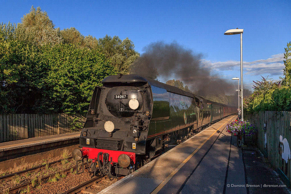 Steam locomotive speeding through a railway station