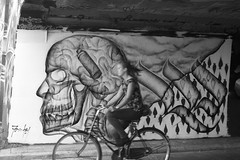 The head and the passer-by (Martijn Martijn) Tags: graffiti art berenkuil eindhoven 040 girl bike bicycle fiets biking fietsen tags street straat straatfotografie streetphotography candid 35mm lens blackandwhite zwartwit bw zw monochrome wwwgevoeligeplatennl