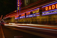 Radio City Music Hall (Brian Aslak) Tags: city nyc newyorkcity light urban usa newyork night traffic unitedstates manhattan trails midtown northamerica metropolis radiocitymusichall neonsigns  50thstreet