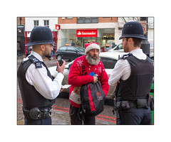 Stop & Search, Islington, North London, England. (Joseph O'Malley64) Tags: stopsearch police policing fatherchristmas santa santaclaus islington northlondon london england uk britain british greatbritain christmasjumper sweater highroad street pavement suspect id identitycard traffic wetweather rain policeconstables workingenvironment laworder thethinblueline christmas christmas2016 beard beards bearded hats helmets antistabvests dutybelts handcuffs securecommunicationsystem metropolitanpolice bobbies bobbiesonthebeat