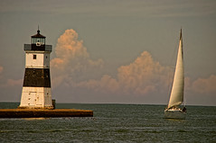 Sailing (Gaby Swanson, Photographer) Tags: lighthouse lake seascape nature sailboat outdoors sailing lakeerie seascapes presqueisle eriepa presqueislelighthouse northpierlighthouse paseascapes northpieratpresqueislestatepark sailingonlakeerie