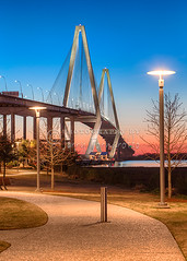 Twilight at Arthur Ravenel Bridge (Jerry Fornarotto) Tags: city travel bridge blue sunset sky orange sc water yellow vertical architecture modern night river landscape outdoors photography lights evening pier arch waterfront suspension dusk vibrant south mountpleasant scenic southcarolina engineering landmark structure architectural diamond cables photograph transportation cooper carolina upright iconic charlestonsc suspensionbridge span fishingpier cooperriver ravenel lowcountry cooperriverbridge ravenelbridge cablestaybridge patriotspoint royalblue newcooperriverbridge cablestay arthurravenelbridge diamondshape jerryfornarotto