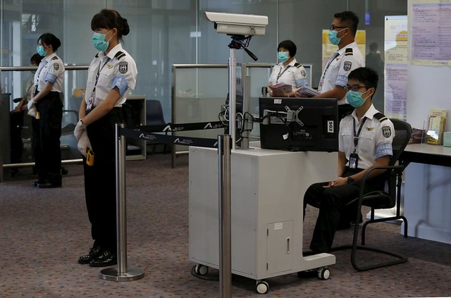 Airport staff wait for arriving passengers for a temperature check at Hong Kong Airport in Hong Kong