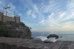 Estudiando Una Nueva Captura (Tomás Hornos) Tags: roca peñón cruz santo almuñécar nubes clouds mar sea azul cielo libro lectura