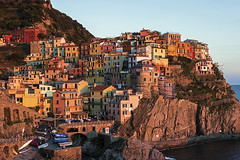 Manarola in Cinque Terre region in Italy (prosiaczeq) Tags: old blue homes sunset sea sky italy cliff heritage water buildings boats dawn coast town site colorful europe afternoon village view stones liguria famous horizon scenic structures historic hills roofs coastal cinqueterre charming picturesque region manarola rugged attraction liguriansea mediterraneansea italianriviera jumble touristic laspezia lpfiery
