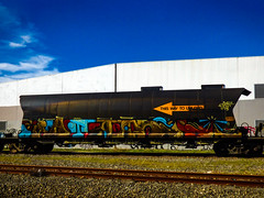 This Way To Unload Aerosols (Steve Taylor (Photography)) Tags: tanker rail railway train thiswaytounload wagon track art graffiti mural streetart tag building brown blue white orange yellow direction newzealand nz southisland canterbury christchurch lines arrow cloud sunny sky sunshine