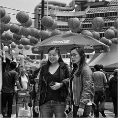 An oriental day in Rotterdam (John Riper) Tags: johnriper street photography straatfotografie square vierkant bw black white zwartwit mono monochrome netherlands candid john riper canon 6d 24105 l library bibliotheek hoogstraat girls women ladies asian oriental chinese coca cola people trolley lanterns lampions smartphones iphones