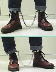 Doc Martens 8-eyes cherry red with leg irons locked on top of boots (asiancuffs) Tags: handcuffs handcuffed shackles shackled boots