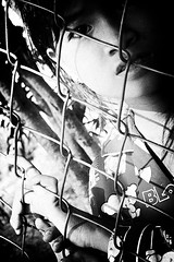 fingers on the fence (khrawlings) Tags: 2010 cambodia canonpowershota720is phnompenh bw blackandwhite monochrome portrait girl contrast face fence metal wire