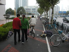 Scenes of Shanghai 4 (GustavoG) Tags: pudong shanghai china sidewalk people walking prostrate elderly beggar woman begging bicycles fromthehip unmodified forsakenpeople poverty