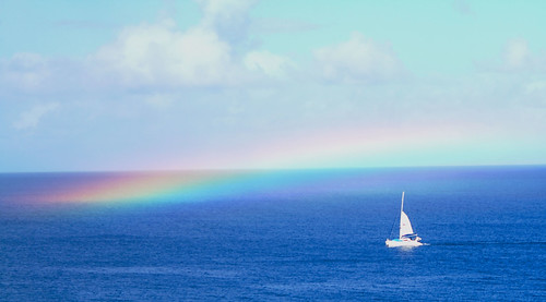 A rainbow spreading on ocean with boat.
