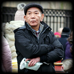 Surveying the scene (* RICHARD M (Over 6 million views)) Tags: chinesenewyear kungheifatchoi chinatown chinatownliverpool candid street portraits portraiture candidportraits candidportraiture streetportraits streetportraiture yearoftherooster chineseman clothcao foldedarms lostinthought liverpool merseyside europeancapitalofculture capitalofculture liverpudlians scousers merseysiders gongheyfatchoy liverpoolchinesenewyear liverpoolchinatown
