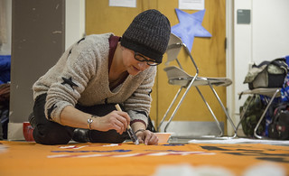 Silke Tudor Paints a Banner in Preparation for an Anti-Torture Demonstration