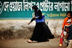 By The Wall That Writes On Itself (N A Y E E M) Tags: younglady burqa hijab child bat cricket light colors graffiti mural today afternoon candid street ashkardighirpar chittagong bangladesh carwindow