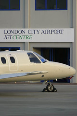 Business Jet parked outside London City Airport 'Jet Centre' (Greg Bajor) Tags: 2003 city uk travel blue sunset england sky holiday london tarmac modern clouds speed plane sunrise airplane fly flying airport wings traffic display action britain dusk aircraft altitude aviation smoke air centre united touch great wing jet kingdom gear down aeroplane landing business journey commercial depart airline arrive commuter fixed docklands gregory scheme departure takeoff runway atmospheric airliner londoncityairport aerospace advanced flaps taxiing livery birdlike bajor wingslet birdlikeimages gregbajor