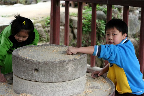 Children playing with a water powered grain wheel