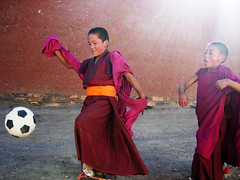 Tibetan child monks enjoy soccer in sunlight (Samer M) Tags: china travel red tibetans boys kids children football asia soccer smiles tibet monks xinjiang xiahe flowing robes buddhists raysoflight rayoflight youngmonks labrangmonastary