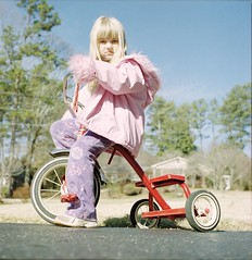 Pink (WadeB) Tags: pink girls red portrait color 1025fav wow child tricycle scowl trike frown mad expired radioflyer corrected fujinph400 yashicamat124g