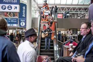 Luke Nephew Leads Witness Against Torture in a Song as the Group Descends an Escalator in Union Station