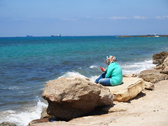 Woman sitting by The sea and reflecting over daily life!