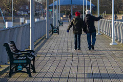 Bring Me Sunshine (fstop186) Tags: man woman couple walking pointing happy winter cold gosport jetty compressedperspective handinhand candid people portsmouthharbour