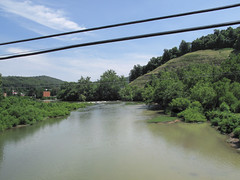 """Plainly visible """"SKY CROSSINGS"""" above the river. (Tim Kiser) Tags: 2010 20100717 barbourcounty barbourcountywestvirginia july july2010 philippi philippiwestvirginia philippicoveredbridge philippilandscape route250 tygartvalleyriver us250 usroute250 westvirginia westvirginialandscape clearcut clearcuthillside deforestation deforestedhillside denudedhillside distantbuildings distanthillside downtown downtownphilippi electriclines hillside landscape mostlysunny northernwestvirginia powerlines river riverlandscape stream view viewfromabridge"""