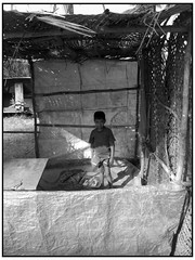 Boy in Shadow (kastakephoto) Tags: travel boy shadow portrait blackandwhite bw sun india house holiday hot travelling face shop pencil canon asian book interesting asia top20portrait photographer top20childportrait legs little indian innocent poor goa young powershot full special hut shade figure flies shack shorts dust s50 palolem enclosure kas