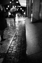 A rainy night (stefankamert) Tags: stefankamert street rain rainy umbrella textures lights dof bw baw sw blackandwhite blackwhite black fujifilm fuji x100 x100s people city blurred exposure alienskin